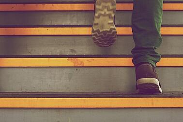 Image of man walking up stairs. Start a culture of improvement in four easy steps.