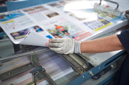 Printing press with glossy prints demonstrating the need for temperature control and viscosity measurement in printing processes.
